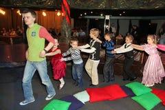 Giochi all'aperto attivi dei bambini sotto la direzione del teatro Smeshariki degli animatori degli attori e di Santa Claus Fotografia Stock
