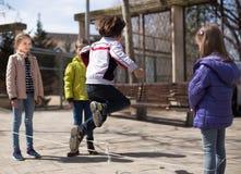 Giochi attivi dei bambini Il ragazzo salta sopra la corda Fotografia Stock Libera da Diritti