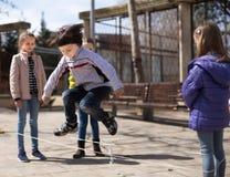 Giochi attivi del ` s dei bambini Il ragazzo salta sopra la corda Fotografia Stock Libera da Diritti