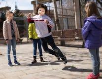 Giochi attivi del ` s dei bambini Il ragazzo salta sopra la corda Fotografie Stock
