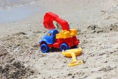 Giochi auto--ekskovator e la pala sulla costa sabbiosa immagine stock