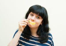 Giochi castana sorridenti della ragazza con la fetta arancio Immagine Stock