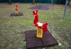 Giochi d'oscillazione per i piccoli bambini oscillazioni rosse a forma di come i piccoli cavalli Campo da giuoco abbandonato immagine stock