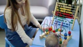 Giochi da bambini con di un giocattolo colorato multi Aiuti della mamma archivi video