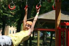 Giochi da bambini con gli anelli del campo da giuoco all'aperto Fotografia Stock