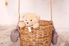 Giochi da bambini con un orso della peluche Giocattoli dei bambini Orsacchiotto che si siede nel canestro del pallone, aerostato  immagini stock