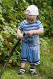 Giochi da bambini con un tubo flessibile di giardino fotografia stock libera da diritti