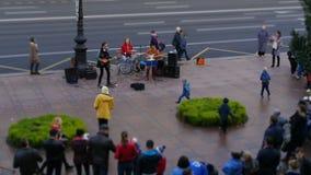 Giochi dei musicisti ambulanti sulla via ai passanti video d archivio