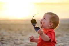Giochi del bambino con gli occhiali da sole Fotografie Stock Libere da Diritti
