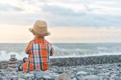 Giochi del bambino sulla spiaggia con i ciottoli fotografie stock libere da diritti