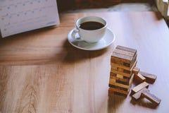 Giochi del blocco e tazze di caffè di legno immagini stock
