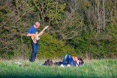 Giochi del chitarrista nel parco all'aperto fotografia stock