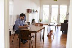 Giochi del figlio del bambino di Uses Laptop Whilst del padre sul pavimento immagine stock