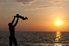 Giochi del padre con il figlio contro un tramonto Fotografia Stock Libera da Diritti