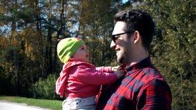 Giochi del papà con la sua piccola figlia, che sta sedendosi in un passeggiatore stock footage