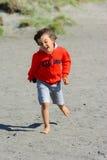 Giochi del ragazzo alla spiaggia immagine stock