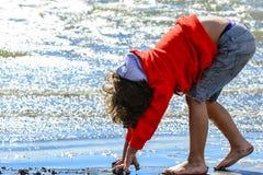 Giochi del ragazzo alla spiaggia Immagini Stock