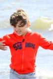 Giochi del ragazzo alla spiaggia fotografia stock