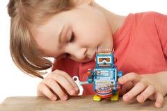 Giochi della bambina con il robot del movimento a orologeria isolato Fotografia Stock