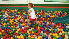 Giochi della bambina nello stagno con le sfere stock footage