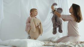 Giochi della figlia e della madre con i giocattoli della peluche video d archivio