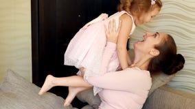 Giochi della madre con sua figlia Gli abbracci della mamma e bacia il suo bambino stock footage