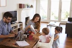 Giochi della madre di Uses Laptop Whilst del padre con i bambini a casa Immagini Stock Libere da Diritti