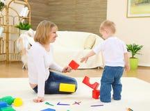 Giochi della mamma con il bambino su un pavimento Fotografia Stock