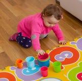 Giochi della neonata del bambino con le tazze colorate Fotografia Stock