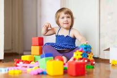 Giochi della ragazza con i giocattoli nell'interiore domestico Fotografia Stock
