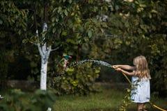 Giochi della ragazza con il tubo flessibile nel giardino immagini stock libere da diritti