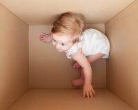 Giochi di bambino piccolo nella scatola Fotografie Stock