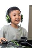 Giochi di computer asiatici del gioco del bambino con il sorriso sul suo fronte Immagine Stock