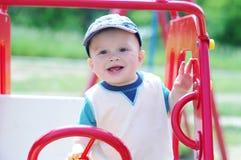 Giochi felici del bambino sul campo da giuoco all'aperto Fotografia Stock
