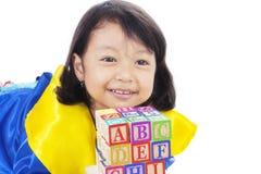 Giochi graduati della bambina con il blocchetto della lettera Fotografia Stock