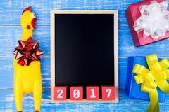 Giochi il pollo giallo, il contenitore di regalo attuale, la lavagna e nuovo y felice Immagini Stock