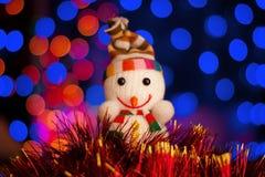 Giochi il pupazzo di neve con le luci della ghirlanda sul fondo variopinto del bokeh Immagine Stock