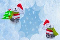 Giochi l'albero con gli ornamenti e due cani bianchi in cappelli rossi che tengono un fiocco di neve blu in bianco per testo Immagine Stock Libera da Diritti