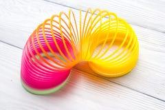 Giochi l'arcobaleno di plastica su un fondo bianco, spirale di colore per gioco Fotografia Stock