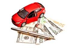 Giochi l'automobile, la chiave ed i soldi sopra bianco Immagini Stock Libere da Diritti