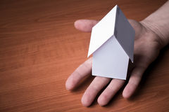 Giochi la casa di carta su una mano umana, copi il fondo dello spazio Fotografia Stock Libera da Diritti