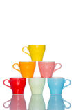 Giochi la tazza variopinta multipla della tazza di caffè sulla tavola della riflessione Immagine Stock