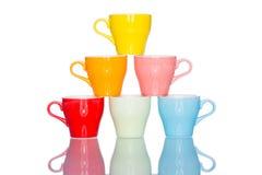 Giochi la tazza variopinta multipla della tazza di caffè sulla tavola della riflessione Immagini Stock