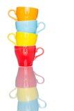 Giochi la tazza variopinta multipla della tazza di caffè sulla tavola della riflessione Fotografia Stock