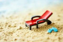 Giochi lo sdraio ed i piccoli flip-flop blu sulla sabbia Immagine Stock