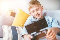 Giochi Preteen del ragazzo con lo smartphone relativo a gamepad che si trova sul sofà accogliente nel salone domestico immagine stock libera da diritti