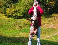 Giochi stafordshirsky del terrier del cane con il proprietario Immagine Stock Libera da Diritti