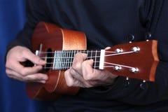 Giochi sulle ukulele, piccola profondità di campo del musicista Immagine Stock