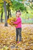 Giochi svegli della bambina con le foglie di autunno Fotografia Stock Libera da Diritti