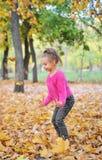 Giochi svegli della bambina con le foglie di autunno Immagini Stock